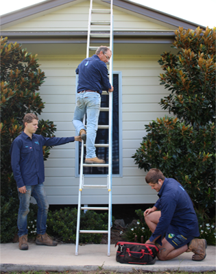 three men, one is climbing the ladder, other act as support, the other one getting the tools